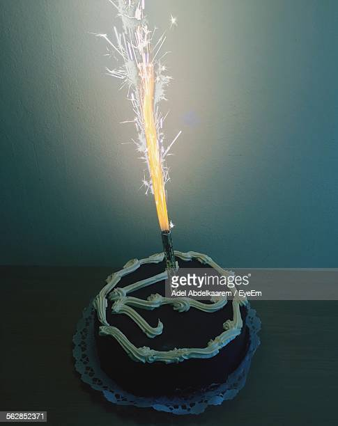 high angle view of birthday cake with burning candle on table - 記念日 ストックフォトと画像