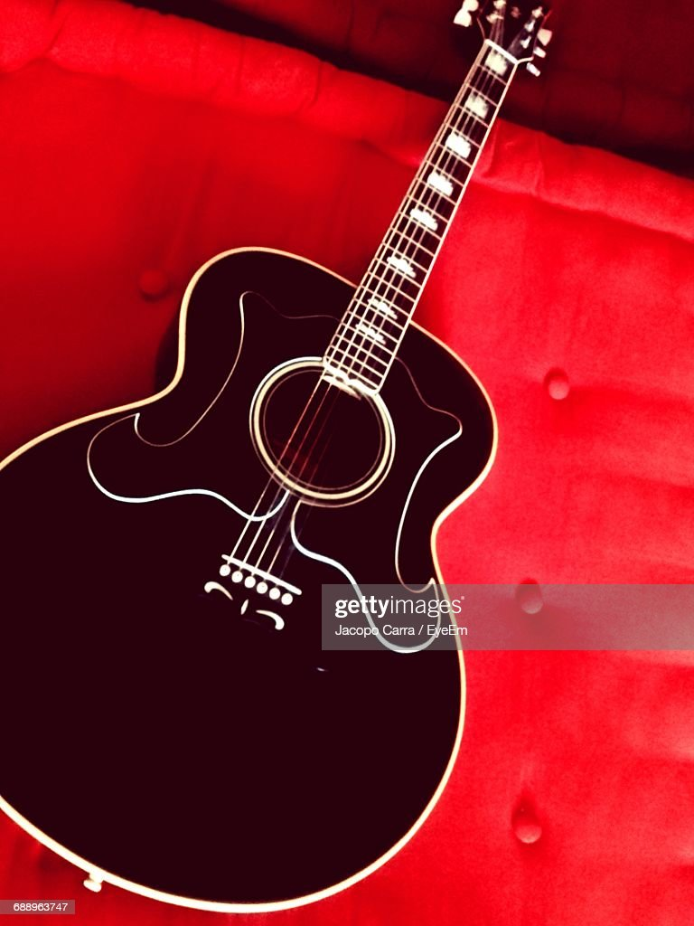 High Angle View Of Black Acoustic Guitar On Red Bed Stock Photo