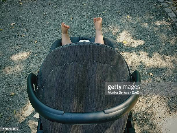 high angle view of black baby carriage with feet up - carriage stock pictures, royalty-free photos & images