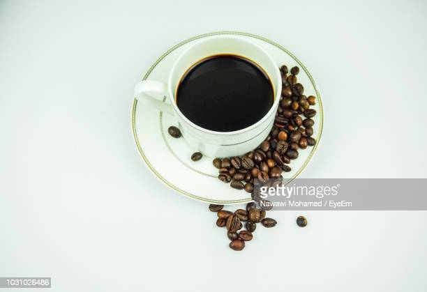 high angle view of black coffee with beans on table - saucer stock pictures, royalty-free photos & images