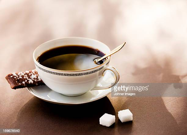 High angle view of black coffee with coffee cookie