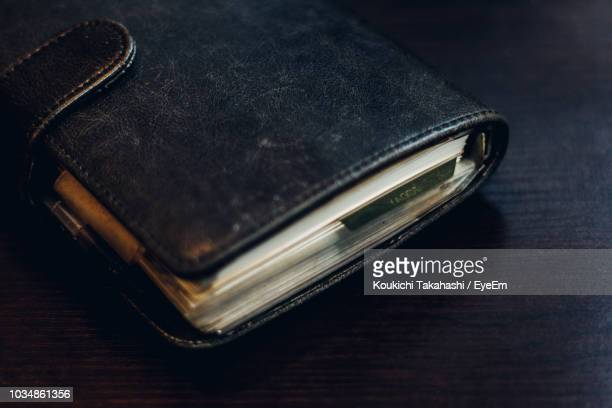 High Angle View Of Black Diary On Table