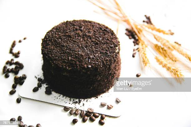 High Angle View Of Black Forest Cake By Coffee Beans And Wheat On White Background