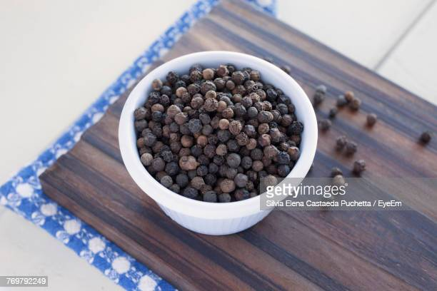 High Angle View Of Black Peppercorn In Bowl On Cutting Board