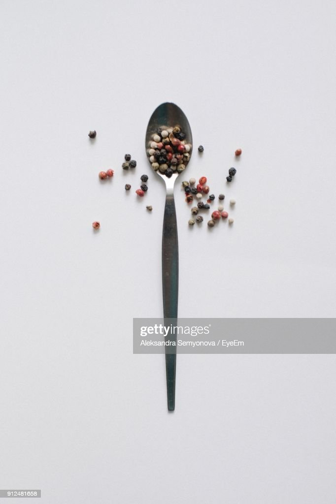 High Angle View Of Black Peppercorn In Spoon Against White Background : Foto de stock