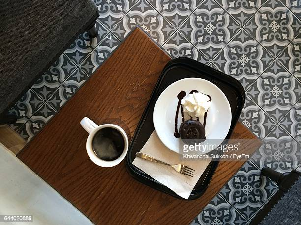 High Angle View Of Black Tea And Pastry On Table