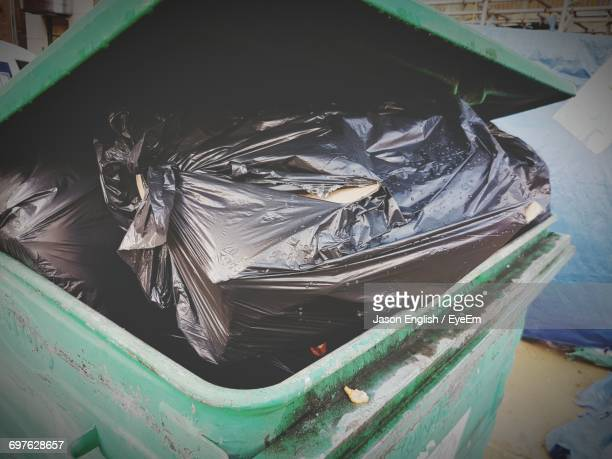 High Angle View Of Black Trash Bag In Green Garbage Can