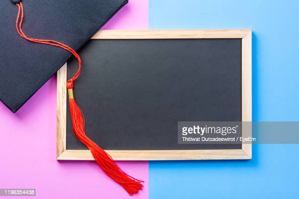 high angle view of blackboard with graduation cap against two tone background - graduation background stock pictures, royalty-free photos & images