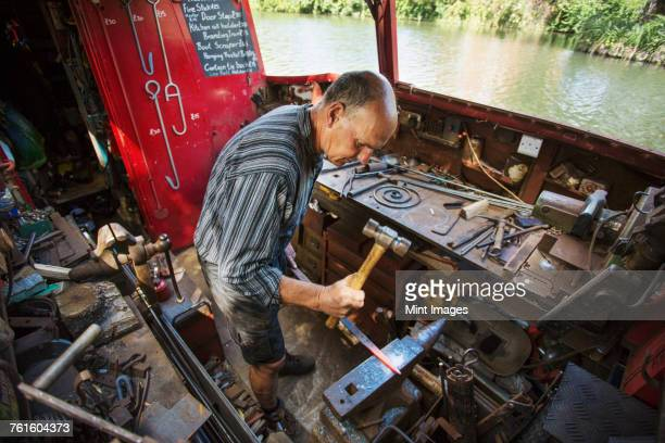High angle view of blacksmith at his workbench on his working boat on the water, hammering hot metal.