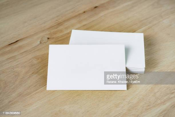 high angle view of blank business cards on wooden table - 名刺 ストックフォトと画像