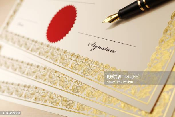 high angle view of blank certificates and fountain pen on wooden table - certificate stock pictures, royalty-free photos & images