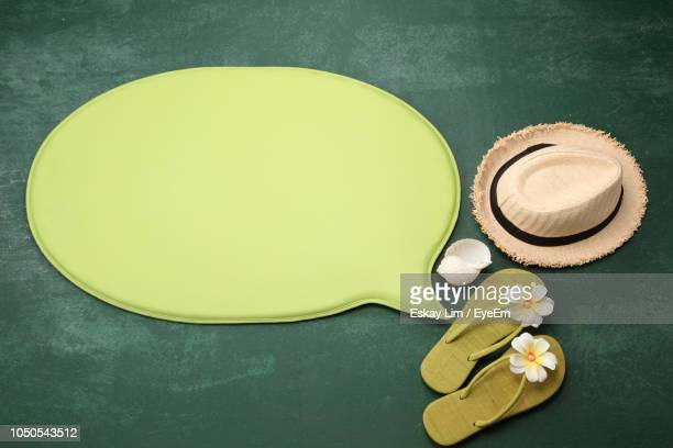 high angle view of blank green speech bubble with flip-flops on blackboard - ciabatta infradito foto e immagini stock
