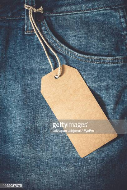 high angle view of blank label hanging on jeans - label stock pictures, royalty-free photos & images