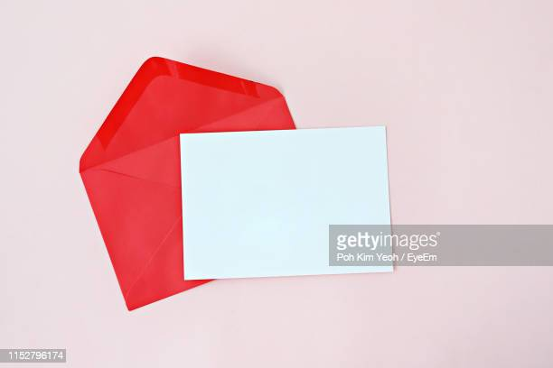 high angle view of blank paper and envelope on table against pink background - envelope stock pictures, royalty-free photos & images