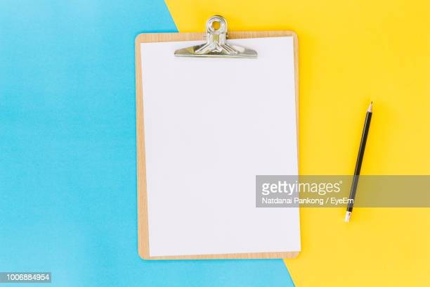 high angle view of blank paper in clipboard with pencil over colored background - clipboard stock pictures, royalty-free photos & images