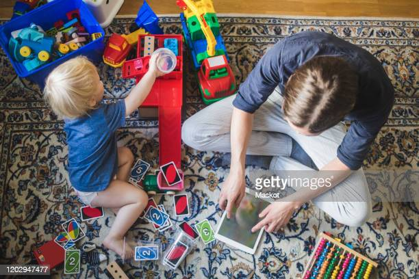 high angle view of blond baby boy playing toys by father using digital tablet in living room at home - family with one child stock pictures, royalty-free photos & images
