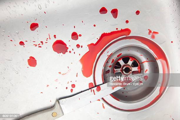 high angle view of blood drops on kitchen knife over sink - blood in sink stock pictures, royalty-free photos & images