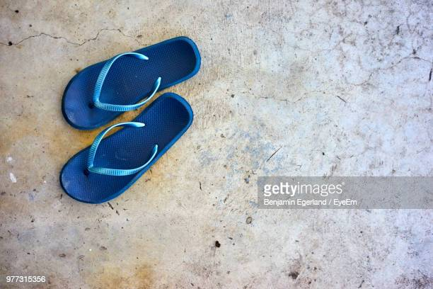 high angle view of blue flip-flops on street - blue shoe stock pictures, royalty-free photos & images