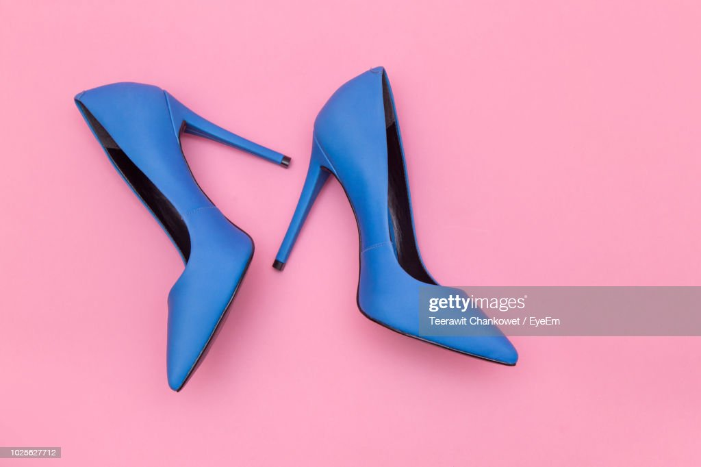 High Angle View Of Blue Stilettos Over Pink Background : Photo
