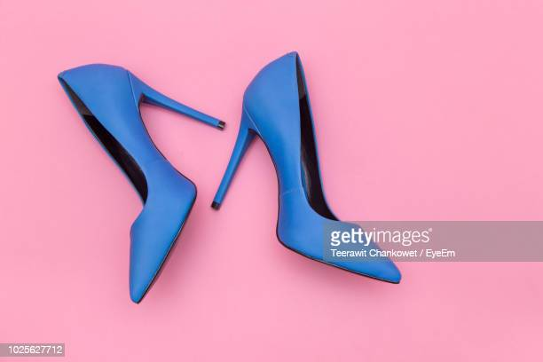 high angle view of blue stilettos over pink background - accessoires stock-fotos und bilder