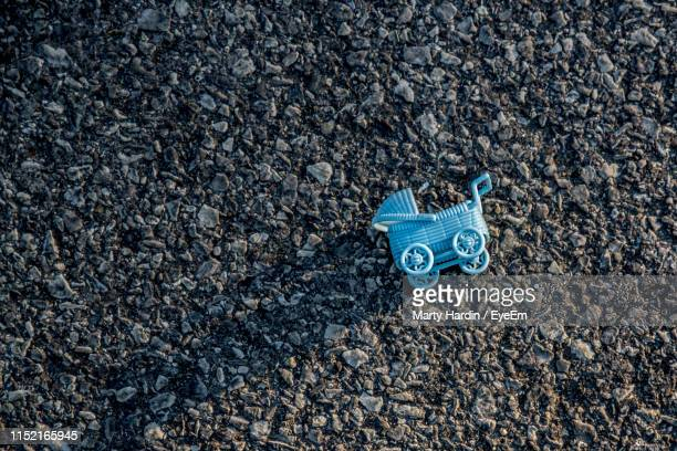 high angle view of blue toy on stones - marty hardin stock photos and pictures