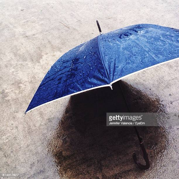 High Angle View Of Blue Umbrella On Wet Street