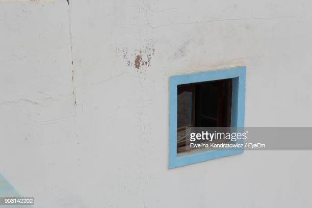 High Angle View Of Blue Window Amidst White Wall