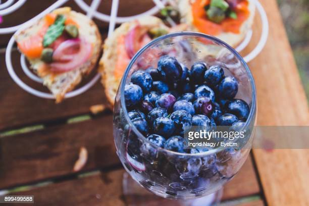 High Angle View Of Blueberries In Wineglass By Food On Rack At Table