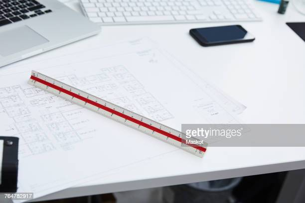 High angle view of blueprints with ruler at desk in creative office