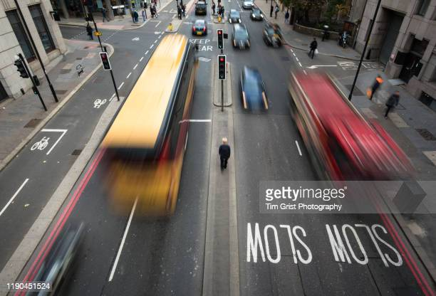 high angle view of blurred vehicles and man walking between traffic on a busy city street. london. uk. - tim grist stock pictures, royalty-free photos & images