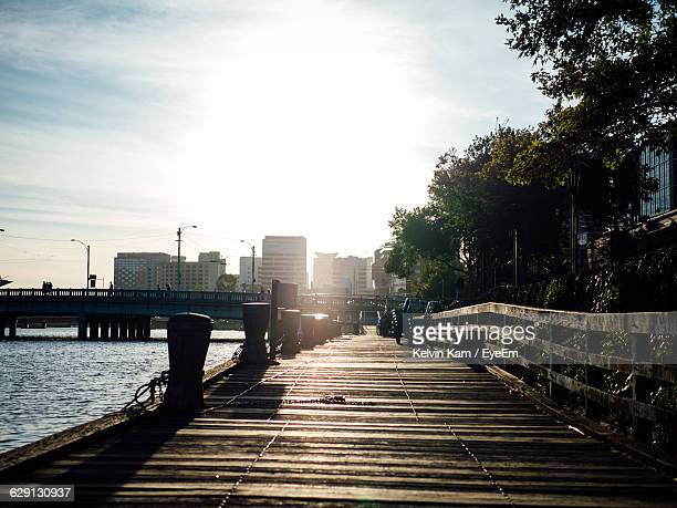 High Angle View Of Boardwalk By River In City Against Sky On Sunny Day