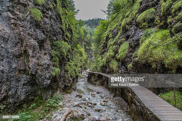 High Angle View Of Boardwalk By Stream Amidst Rock Formations
