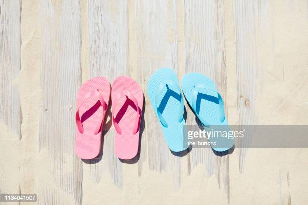high angle view of boardwalk with sand and flip-flops - ペア ストックフォトと画像