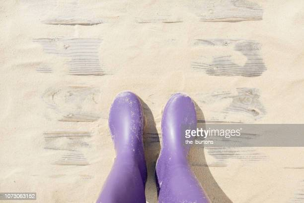 high angle view of boardwalk with sand and lavender colored rubber boots, woman standing in rubber boots on way to the beach - purple boot stock photos and pictures