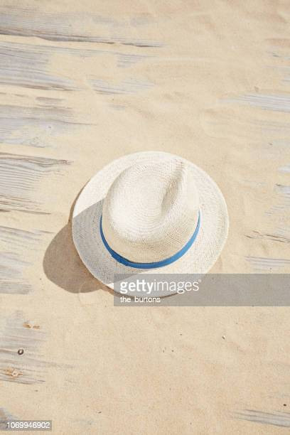 high angle view of boardwalk with sand and straw hat - straw hat stock pictures, royalty-free photos & images