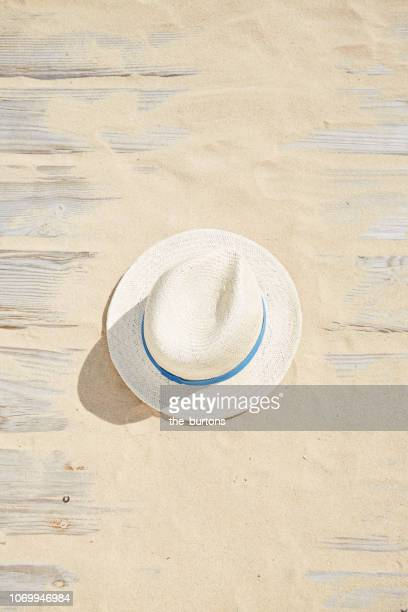 high angle view of boardwalk with sand and straw hat - chapeau photos et images de collection