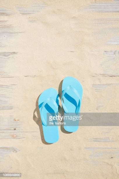 high angle view of boardwalk with sand and turquoise flip-flops - open toe stock pictures, royalty-free photos & images