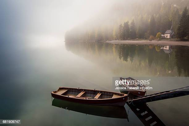 High Angle View Of Boat Moored In Calm Lake During Foggy Weather