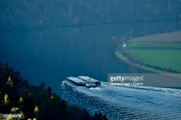 high angle view of boat on river danube - gerhard hagn stock-fotos und bilder