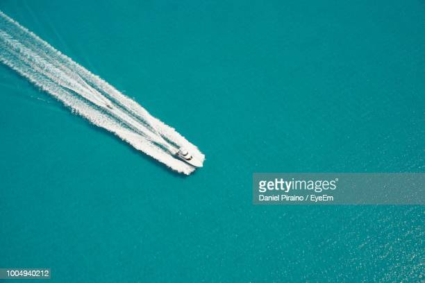 high angle view of boat sailing on sea - wassersport stock-fotos und bilder
