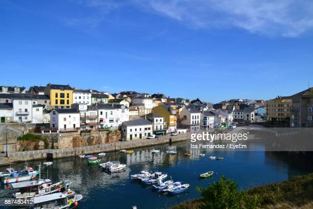 high angle view of boats moored at harbor in city - asturien stock-fotos und bilder
