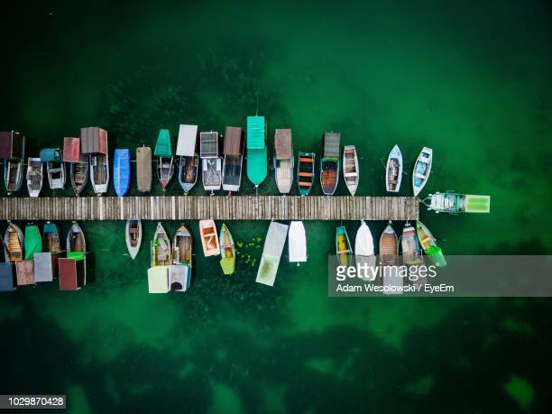 high angle view of boats moored at harbor on sea - augsburg stock-fotos und bilder
