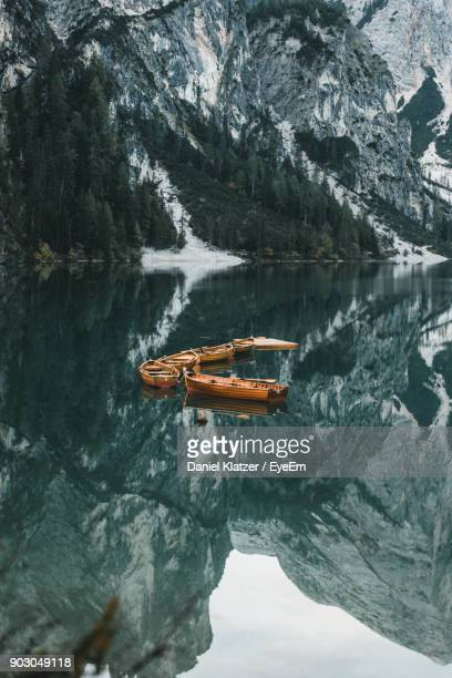high angle view of boats on lake against mountains - pragser wildsee stock pictures, royalty-free photos & images