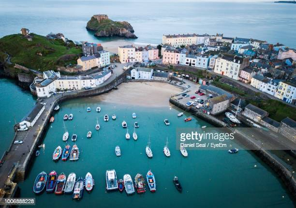 high angle view of boats on sea by city - wales stock-fotos und bilder