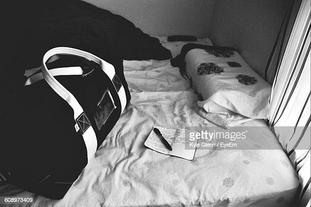 High Angle View Of Book And Luggage On Bed At Home