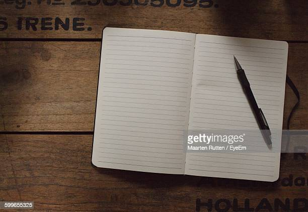 High Angle View Of Book And Pen On Desk