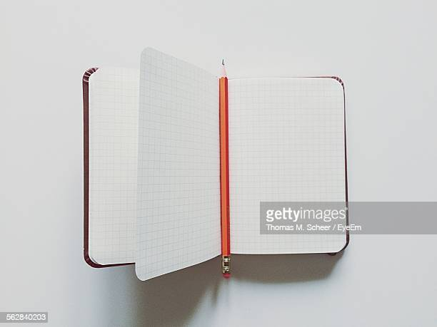 High Angle View Of Book And Pencil Against White Background