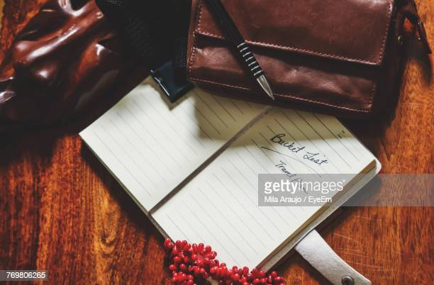 High Angle View Of Book By Pen And Purse On Wooden Table