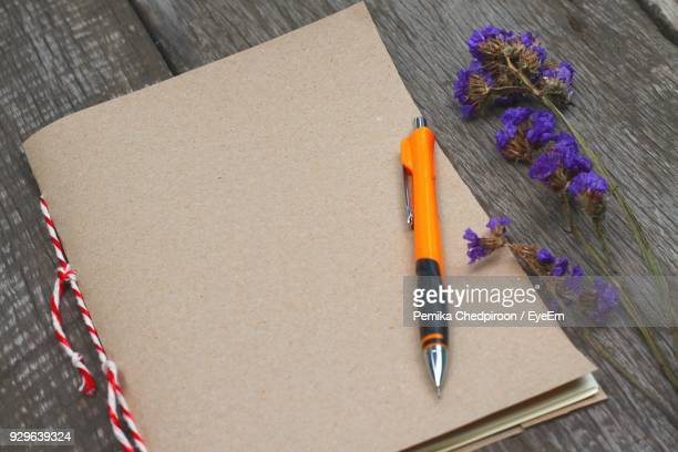 High Angle View Of Book With Pen And Flowers On Wooden Table