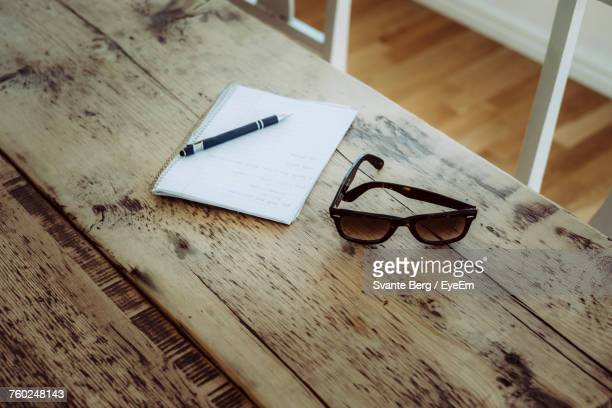 High Angle View Of Book With Pen And Sunglasses On Wooden Table